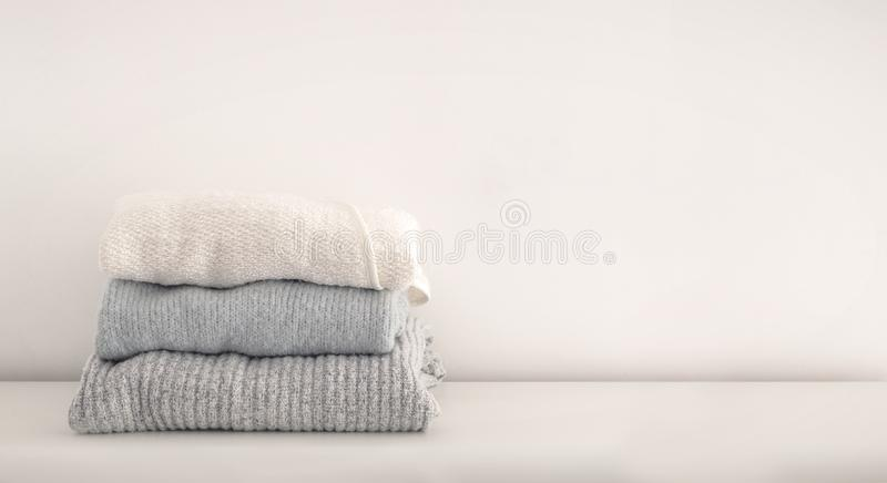 Stack of neatly folded woolen knitwear. Minimal lifestyle, capsule wardrobe. Autumn-winter wardrobe concept. Light and stock photos