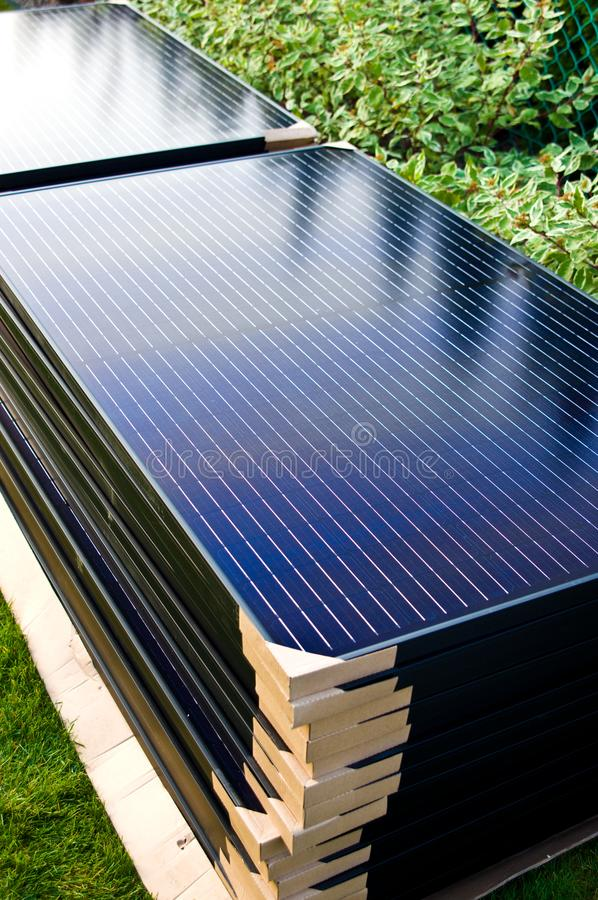 Stack of new solar panel ready for installation. A stack of modern black halfcut technology solar panels ready for installation, stacked in the backyard of a royalty free stock image