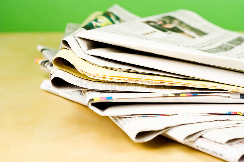Stack of newspapers in color on green background stock photos