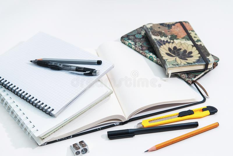 Stack of notebooks and sketchbooks, pencils and pens on a white background royalty free stock images