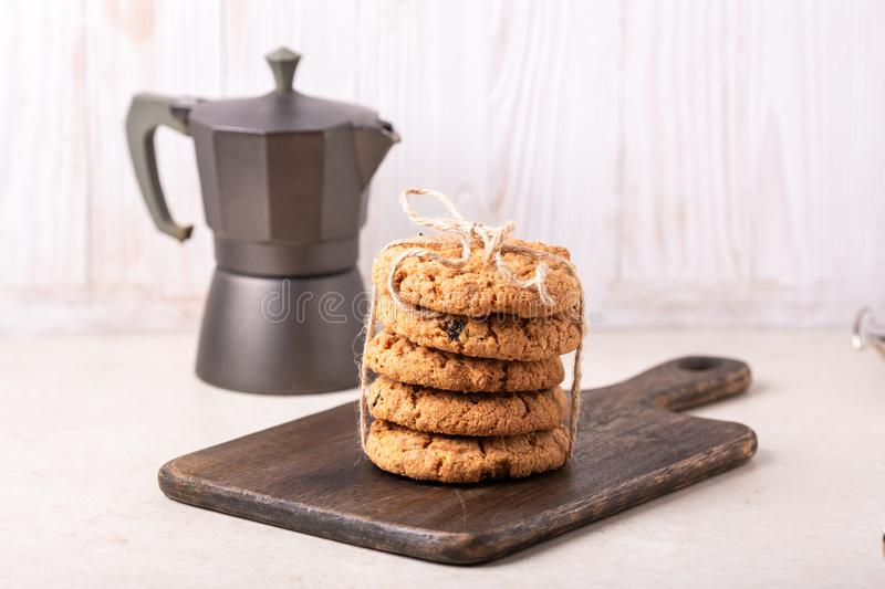 Stack of oatmeal cookies, coffee maker on white wooden background Homemade bakery royalty free stock photos