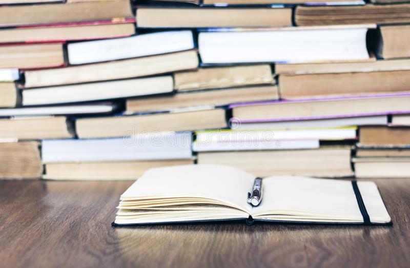 Stack of old book, open notebook and pen. Education concept background, many books piles with copy space for text royalty free stock photography