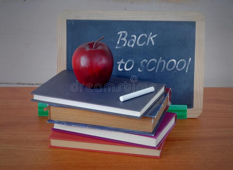 Stack of old books with an apple, a blackboard, chalk and a ruler in front of wooden background. Back to school message. royalty free stock photography