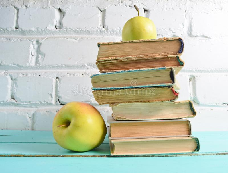 Stack of old books, apple on a white brick wall background. School concept, education stock photo