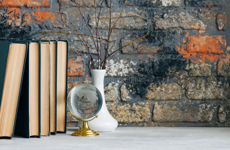 Stack of old books, branches in vase, glass globe, grunge brick stock photography