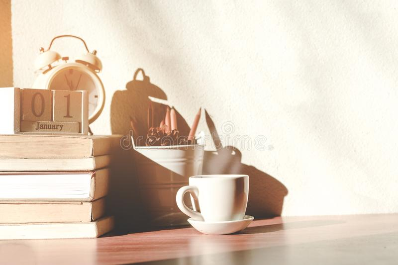 Stack old books with a cup of freshly coffee, vintage alarm clockon, wooden calendar, on table in sunlight morning, Start up stock photos