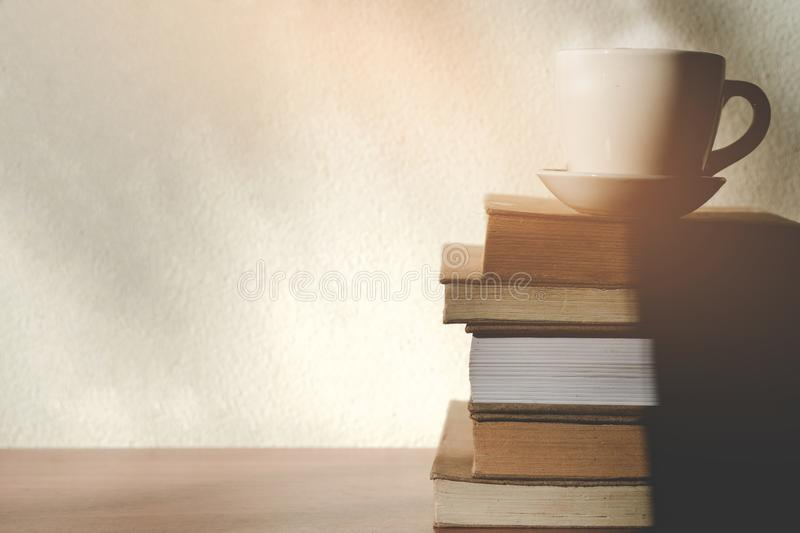 Stack old books with a cup of freshly coffee on wooden table in sunlight morning stock images