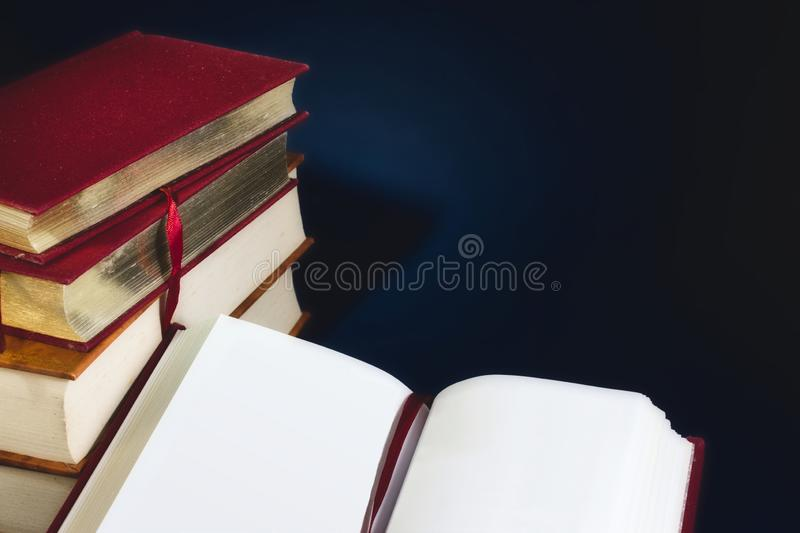 Stack of old books and an open book with blank empty pages against a dark blue background royalty free stock images