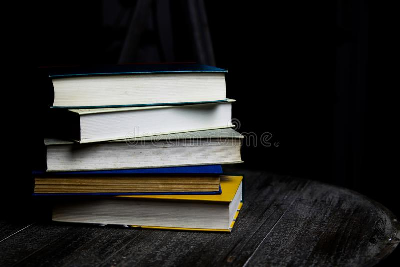 Stack of old books on round wood table with reading light during night royalty free stock image