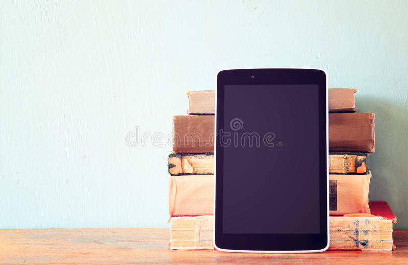 Stack of old books and tablet over wooden shelf. new technology concept. room for text. Stack of old books and tablet over wooden shelf. new technology concept stock photos