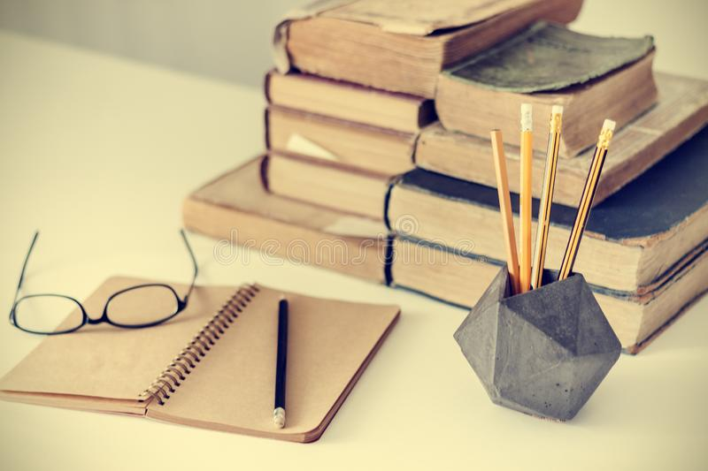 Stack of old books, textbook, glasses and pencils in office background for education retro concept royalty free stock image