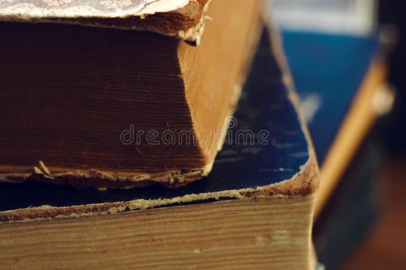 A stack of old books with torn covers. Stack of old vintage multi-page books with shabby covers of different colors stock images
