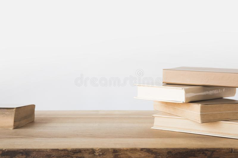 Stack of old books on wooden table on white stock image
