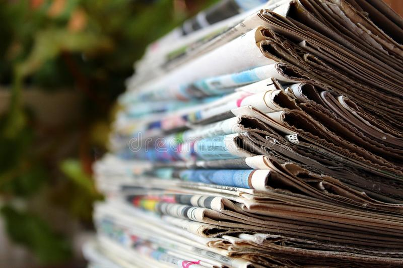 A stack of old newspapers lie on a table. Newspaper, stack, newspapers, background, news, paper, media, white, pile, headline, information, communication, text royalty free stock photos
