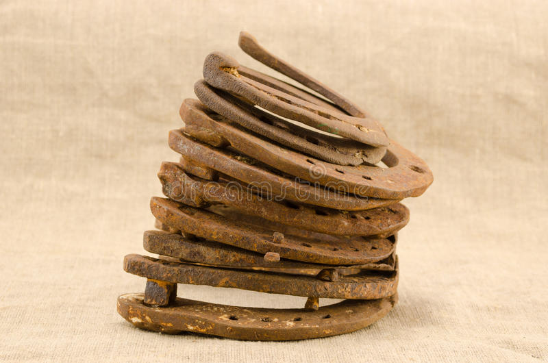 Stack Of Old Retro Horse Shoes On Linen Background Stock Images