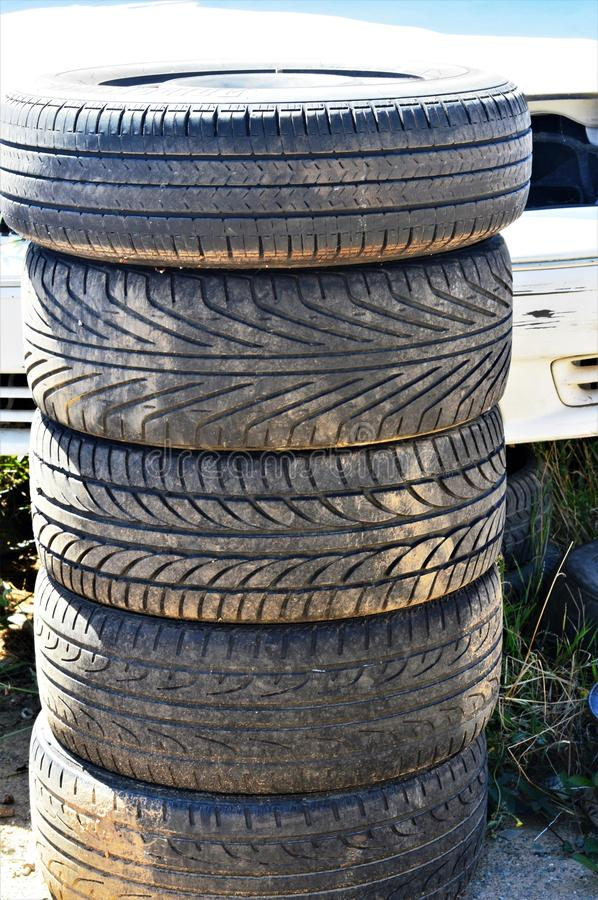 Stack of old tires. Five worn and aged tires of different sizes and styles are stacked on top of each other with part of a car in the background royalty free stock photos