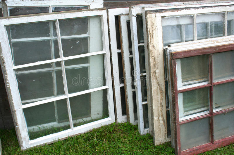 Stack of Old Windows. Old windows and frames are stacked against each other in the grass waiting to be sold at auction royalty free stock photo