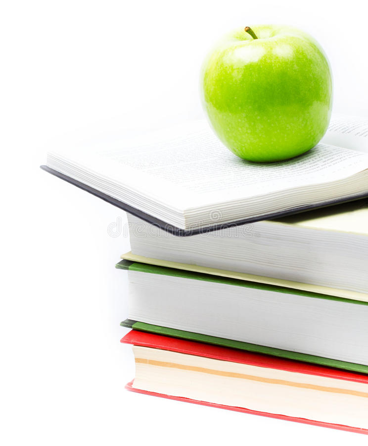 Stack of open books with green apple on white background. Back stock image