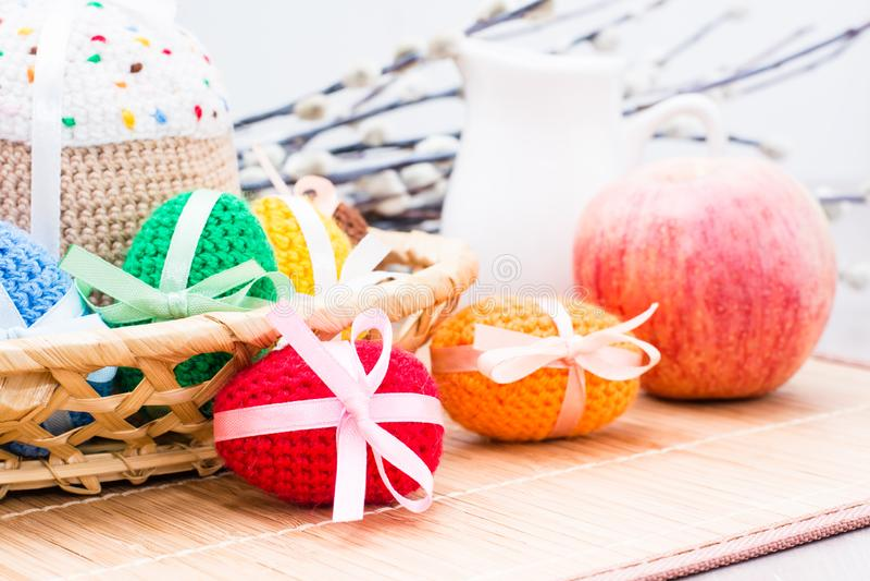 Stack påskägg och en kaka i en korg, ett äpple, en tillbringare och en pil arkivbilder