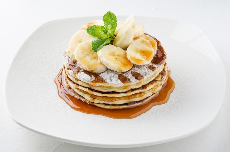 A stack of pancakes with banana slices and caramel sauce, decorated with mint. stock photography