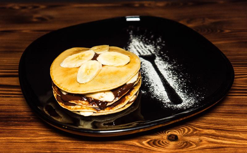 Stack of pancakes with banana slices and chocolate syrup on a plate royalty free stock photography
