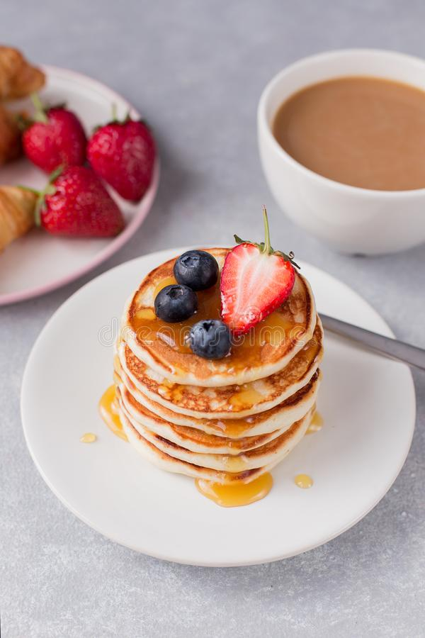 A stack of pancakes with berries and honey, croissant and cup of coffee on gray background royalty free stock photos