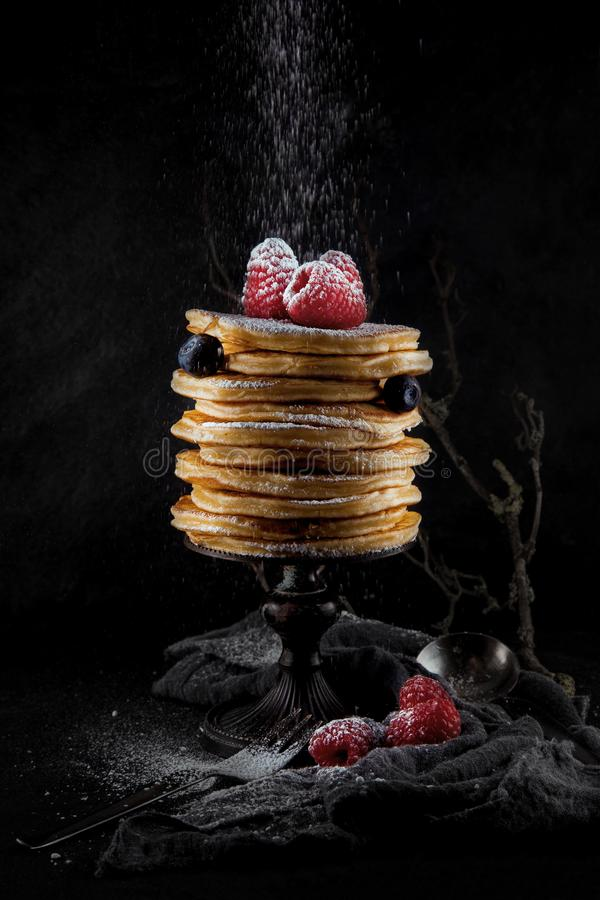 A stack of pancakes decorated with berries and powdered sugar, rustic studio shot royalty free stock photos