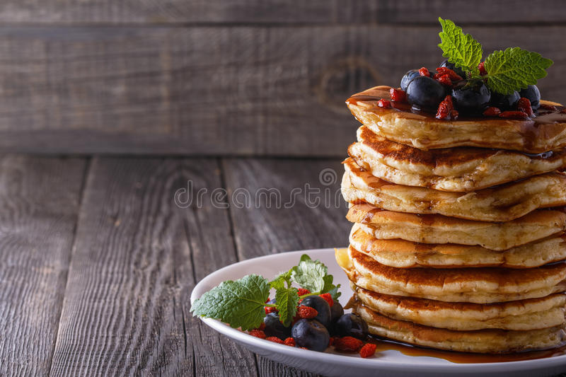 Stack of pancakes with fresh blueberry, goji and maple syrup. royalty free stock images