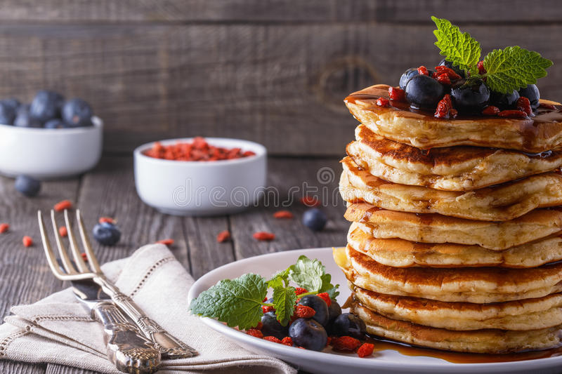 Stack of pancakes with fresh blueberry, goji and maple syrup. stock photography