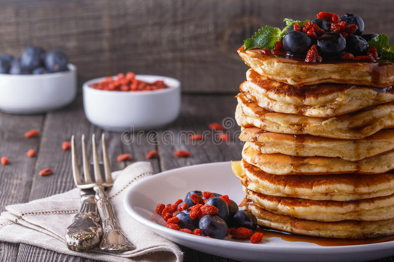 Stack of pancakes with fresh blueberry, goji and maple syrup. Stack of pancakes with fresh blueberry, goji berries and maple syrup royalty free stock image