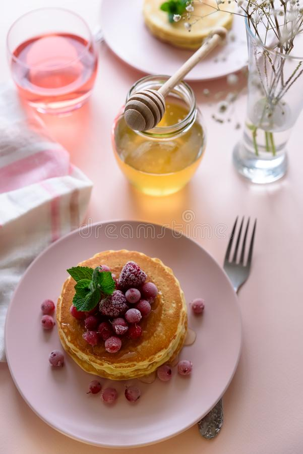 Stack of pancakes with frozen raspberry, red currant and honey on pink background. Selective focus royalty free stock photography