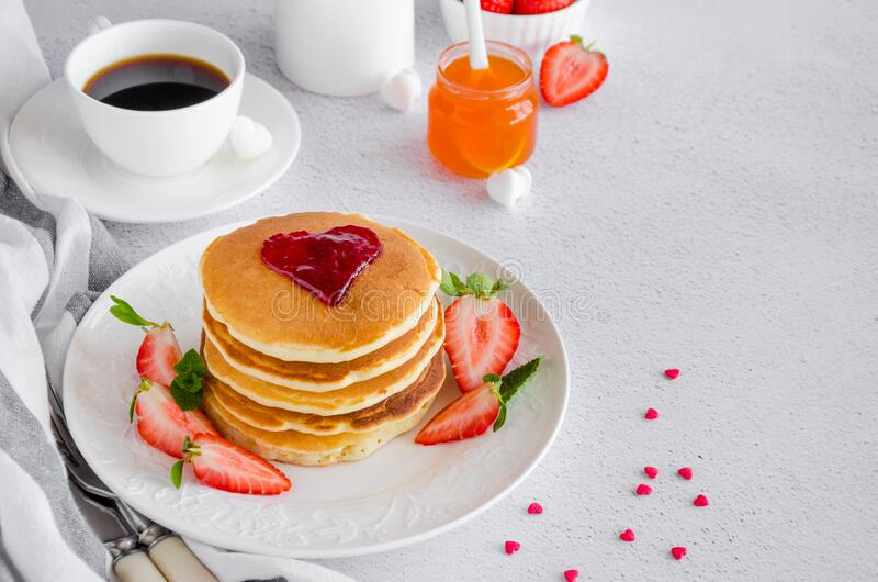 A stack of pancakes with a heart of jam on top with fresh strawberries and mint on a white plate on a light background. Breakfast for Valentine`s Day royalty free stock photos