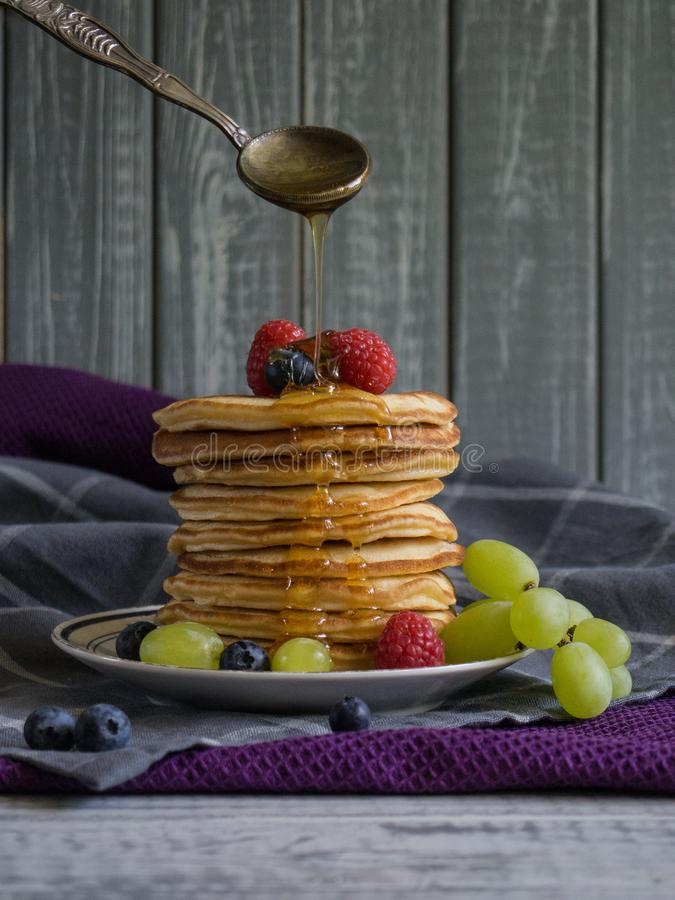Stack of pancakes on a plate with berries and honey pouring above from a spoon stock photos