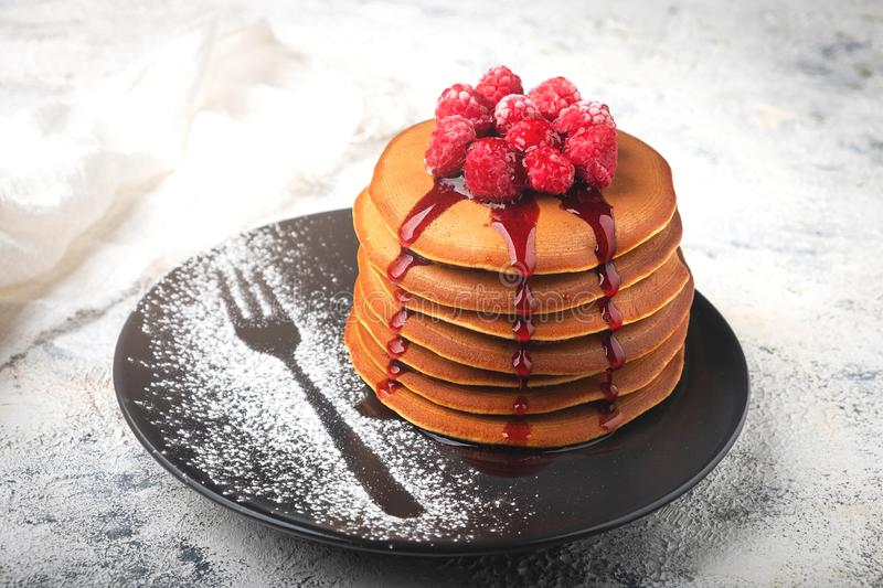 A stack of pancakes on a plate with raspberries and berry sauce royalty free stock image