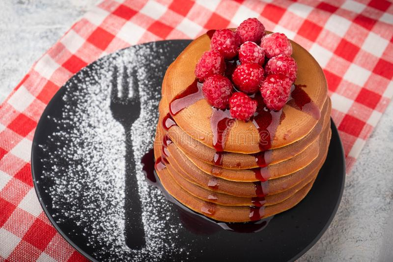 A stack of pancakes on a plate with raspberries and berry sauce stock photos