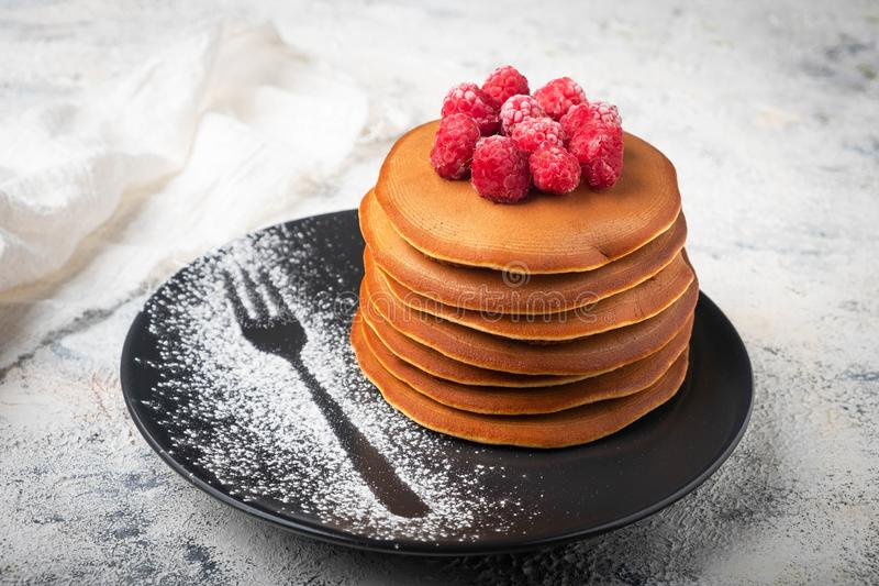 A stack of pancakes on a plate with raspberries and berry sauce stock image