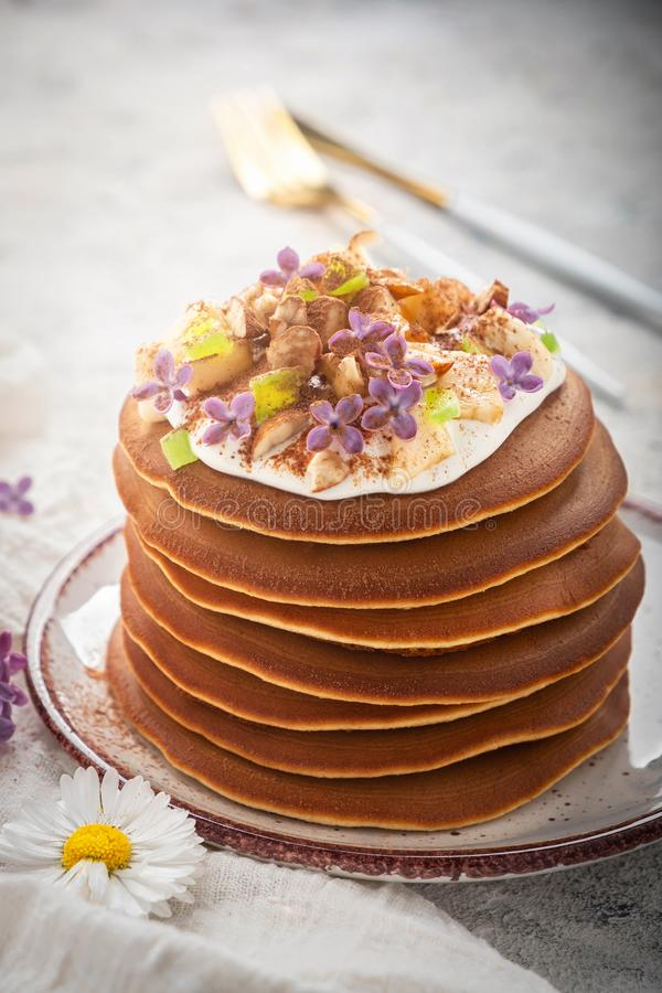 A stack of pancakes on a plate with sauce, bananas, candied fruits and decorated with flowers, Close-up, royalty free stock images