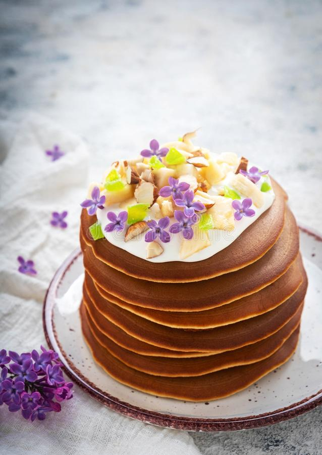 A stack of pancakes on a plate with sauce, bananas, candied fruits and decorated with flowers, Close-up, royalty free stock photos