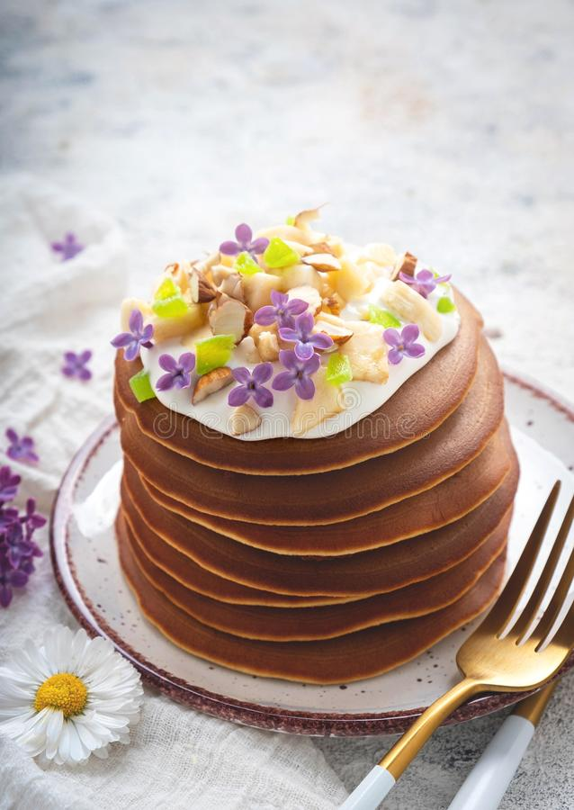 A stack of pancakes on a plate with sauce, bananas, candied fruits and decorated with flowers, Close-up, stock photo