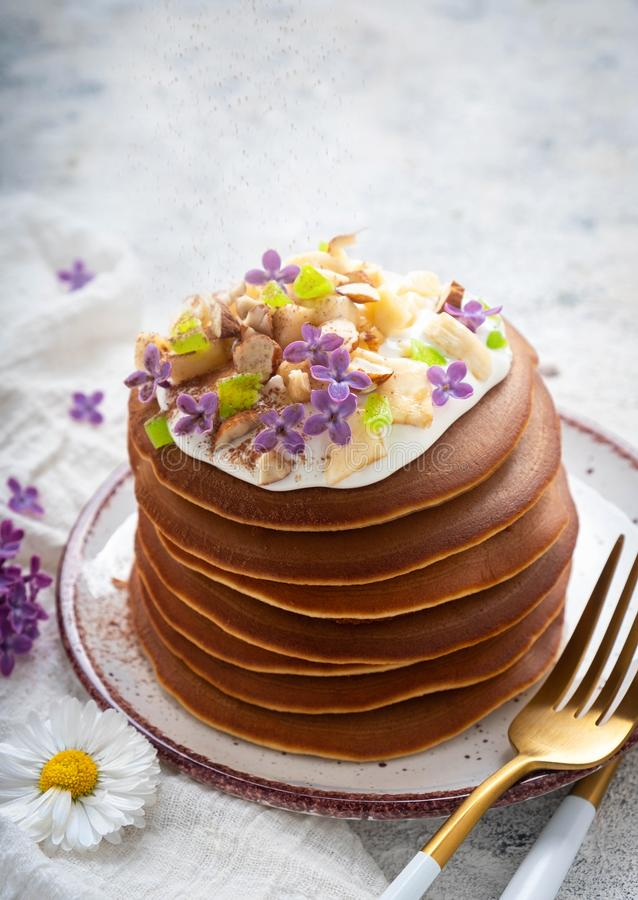A stack of pancakes on a plate with sauce, bananas, candied fruits and decorated with flowers, Close-up, stock images