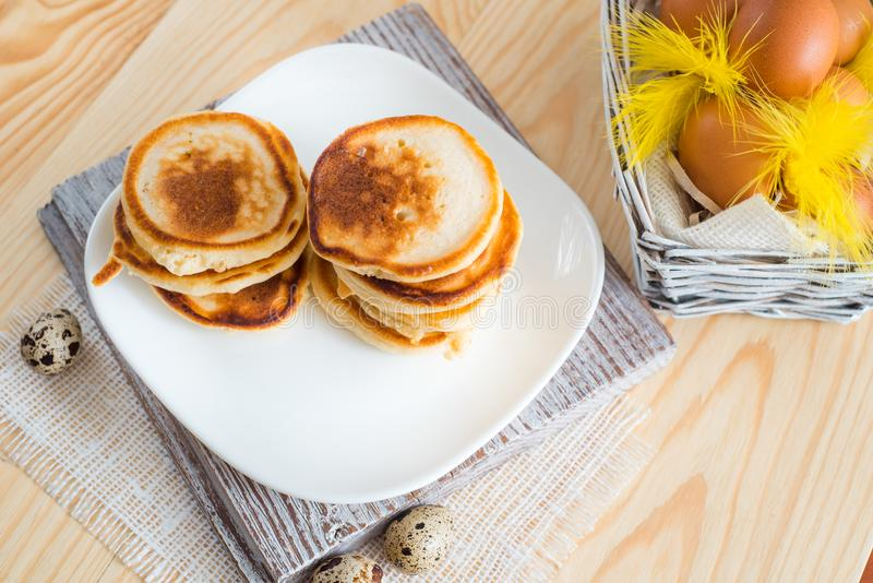 Stack of pancakes in white saucer on light wooden table. On a white plate, On a white plate. Easter eggs, yellow feathers royalty free stock photo