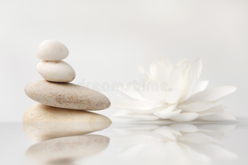Stack of pebbles and white lily, reflection. Wellness still life pebbles and white lily, reflection in water, with waves,high key studio shot stock photography