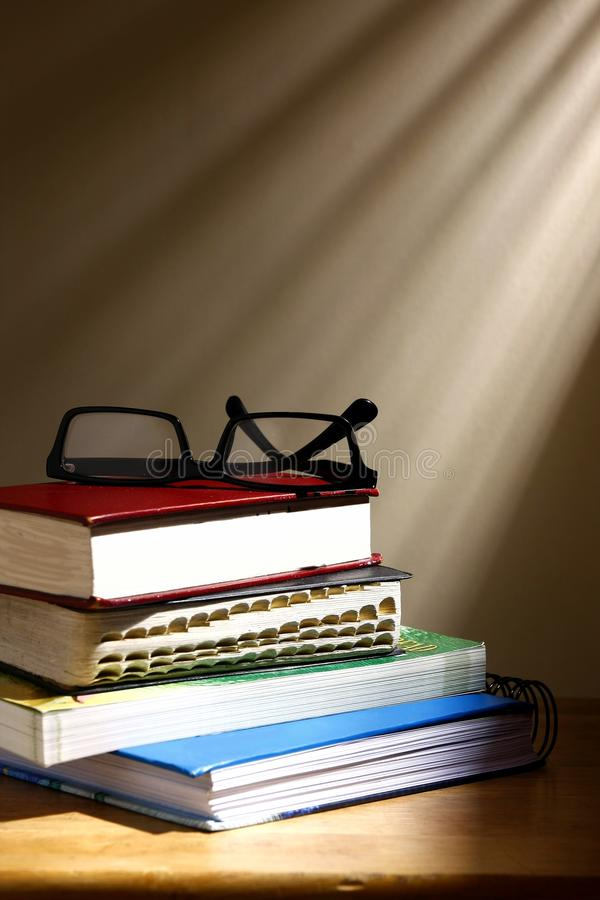 Stack or pile of books and eyeglasses on a wooden table royalty free stock photos