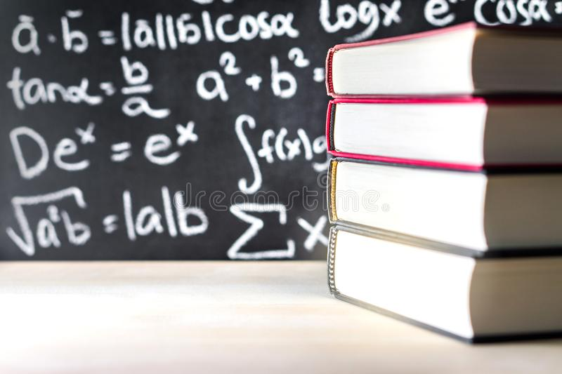 Stack and pile of books in front of a blackboard in school. Math equation written on chalkboard stock image