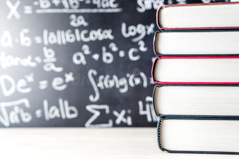 Stack and pile of books in front of a blackboard in school. Math equation handwritten on chalkboard royalty free stock image