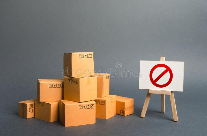 A stack pile cardboard boxes and a sign stand with red symbol NO. Restriction on the importation of goods, proprietary stock photography