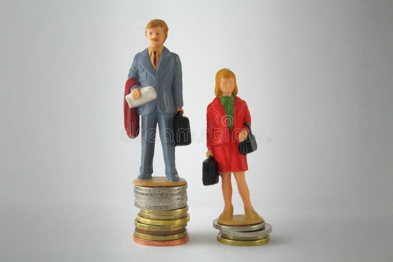 Stack pile of coins with miniature man and woman. Gender pay discrimination concept. Wage disparity between men and women stock images