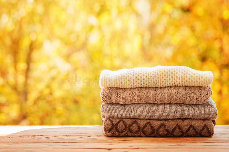 Stack pile of knitted autumn clothes on nature background. stock photos