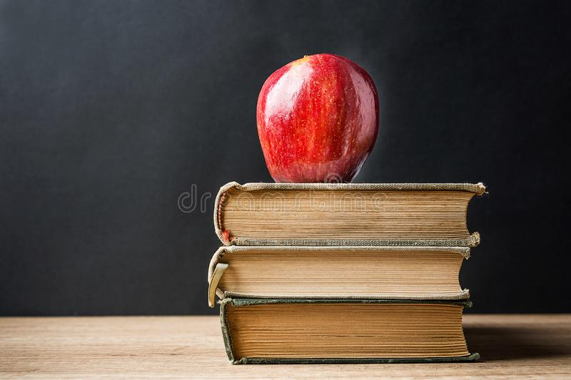 Stack Pile of Old Books Red Glossy Apple on Top. Learning Education Knowledge Concept. Blackboard Background. Classrom. royalty free stock photo