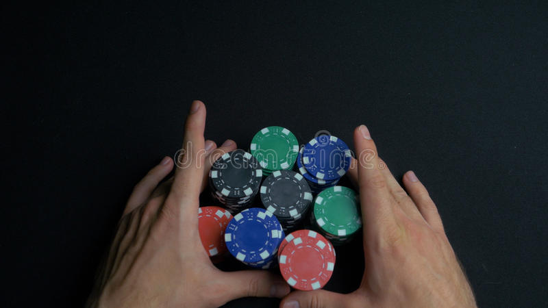 Stack of poker chips and two hands on table. Closeup of poker chips in stacks on green felt card table surface. Poker royalty free stock photos